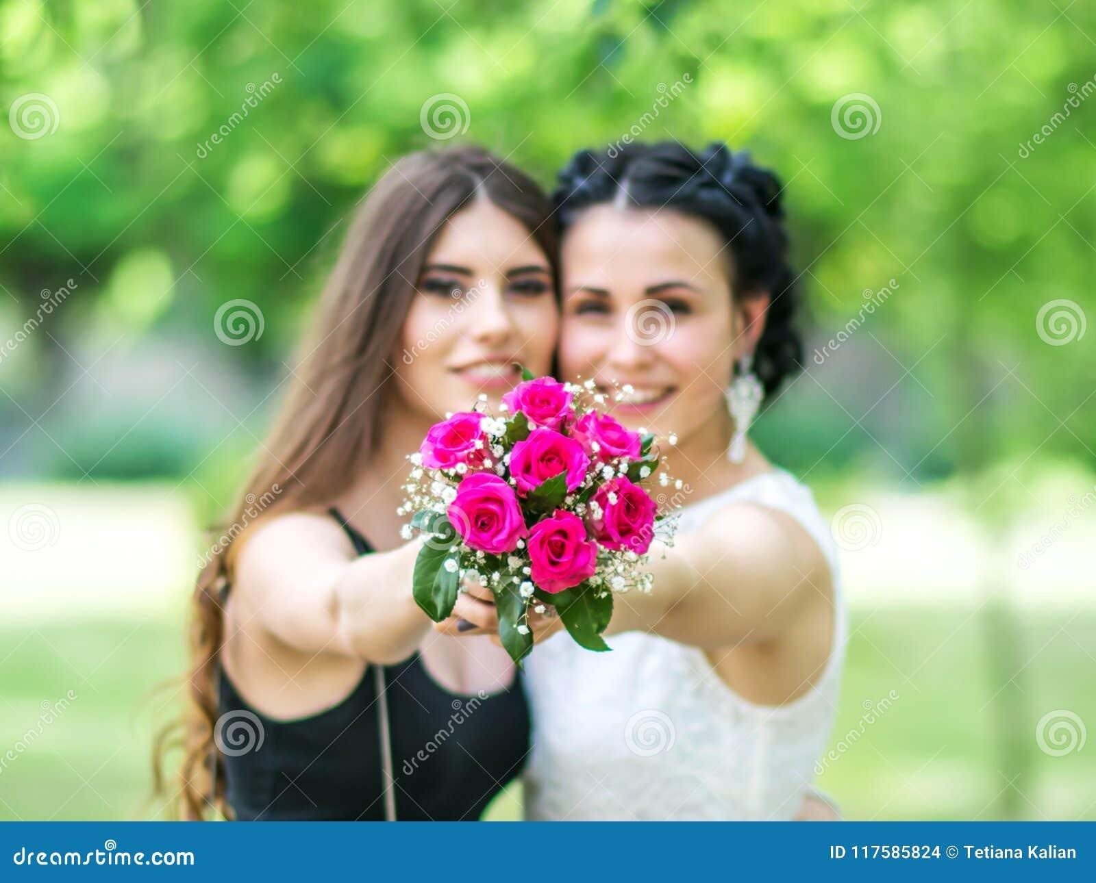Defocused Porträt von zwei schönen jungen Frauen, die Hochzeitsblumenstrauß zusammenhalten und in Kamera grünem Park betrachten B