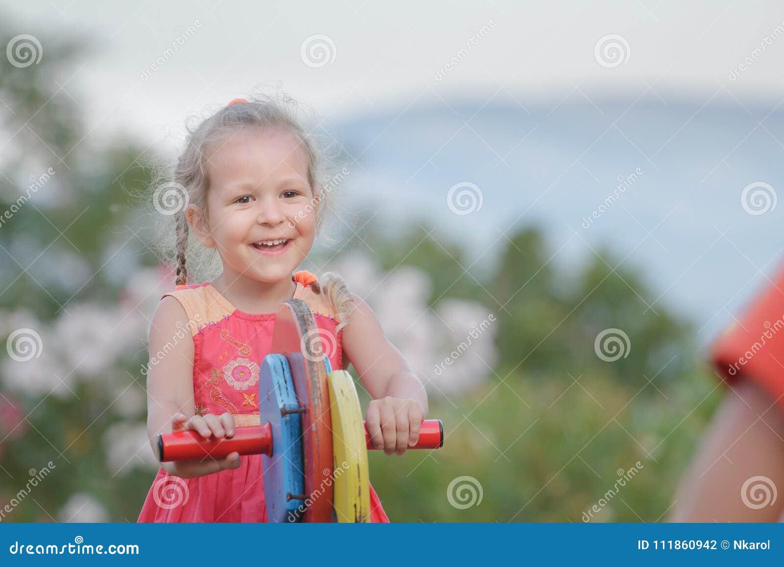 Dehors vacances de peu de fille d enfant balançant sur l équipement en bois de terrain de jeu