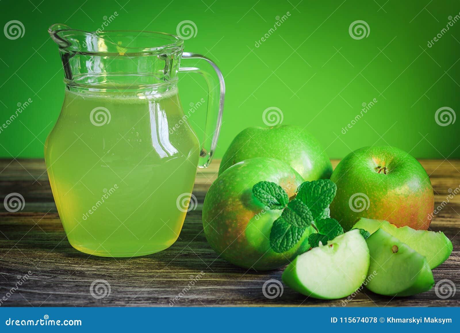 Dekantator jabłczany sok z zielonymi jabłkami na drewnianym stole, zakończenie