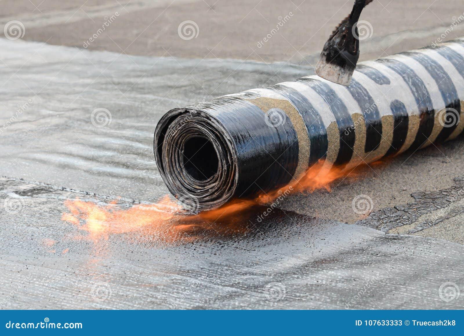 Dekarstwo instalacja czująca z ogrzewaniem i roztapiającą bitum rolką pochodnią na płomieniu, zbliżenie szczegółu krótkopęd