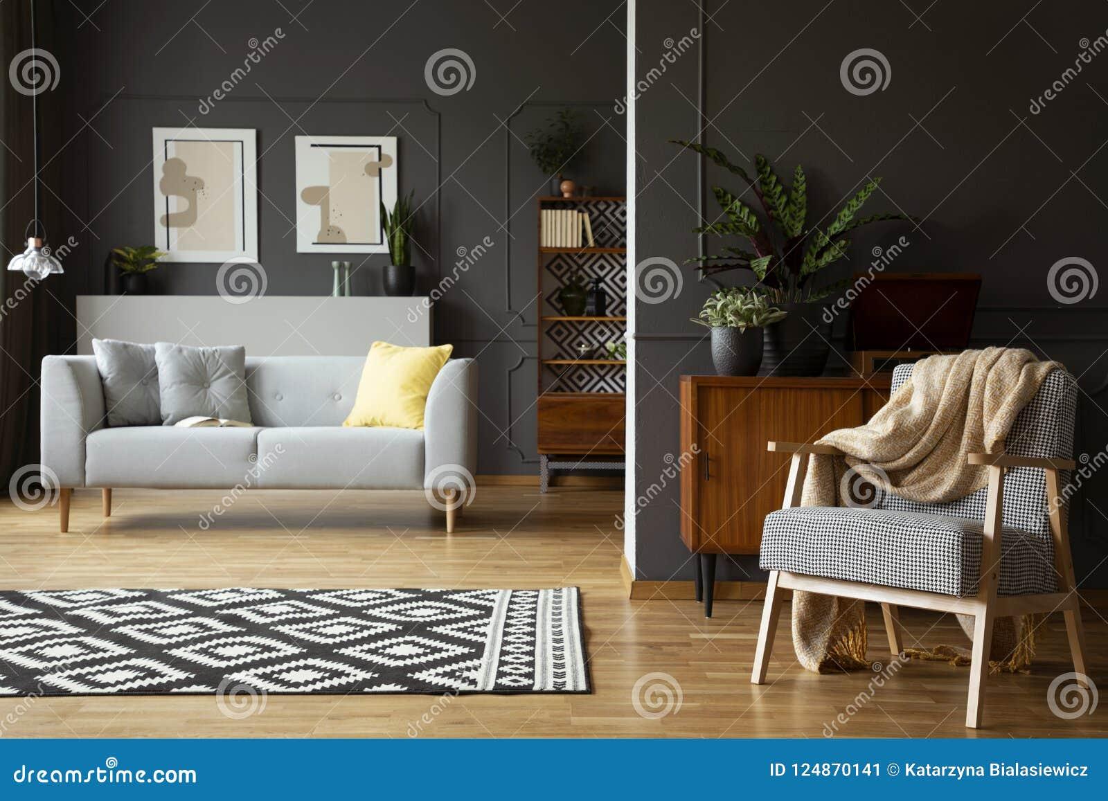 Deken op leunstoel in woonkamerbinnenland met gevormd tapijt, grijze bank en affiches Echte foto
