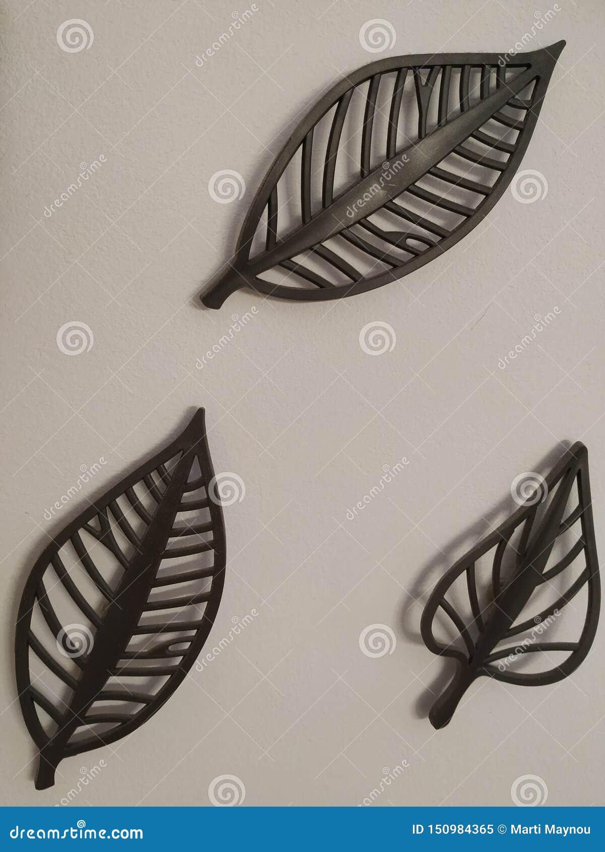 Dekoracyjni metalu trzy liście na biel ścianie