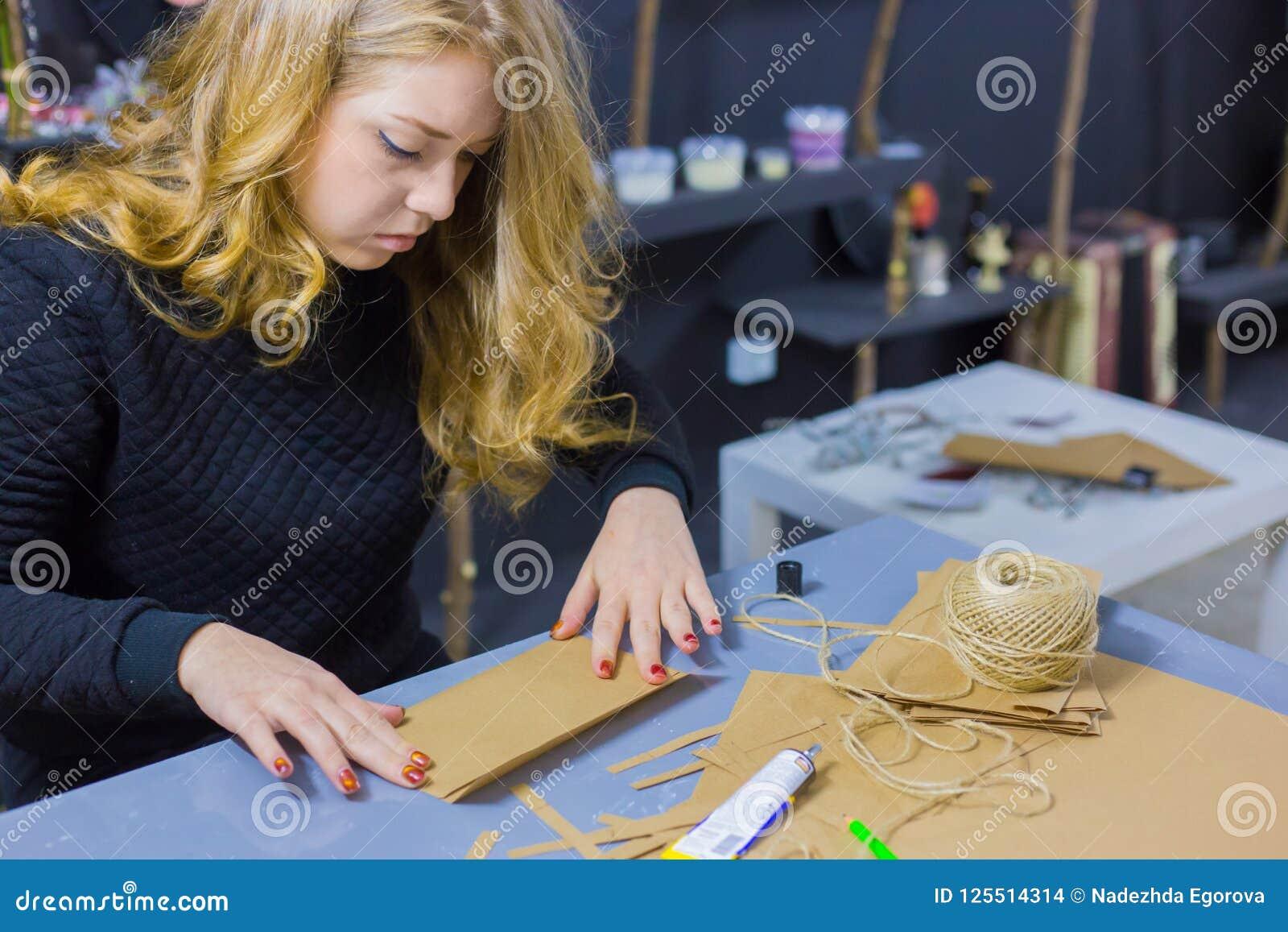 Dekoratör för yrkesmässig kvinna som arbetar med kraft papper