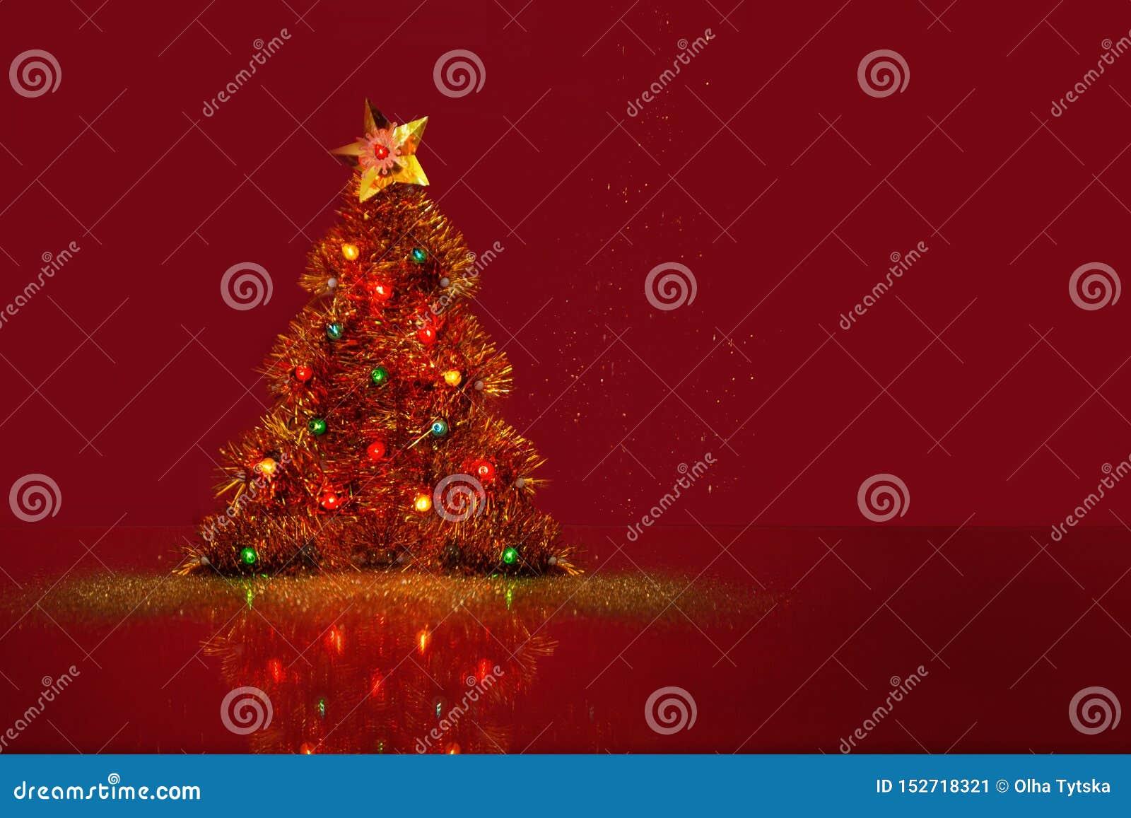 Dekorativ julgran med en skinande liten ljus kula Röd bakgrund med ett utrymme för text Begrepp f?r `s f?r nytt ?r