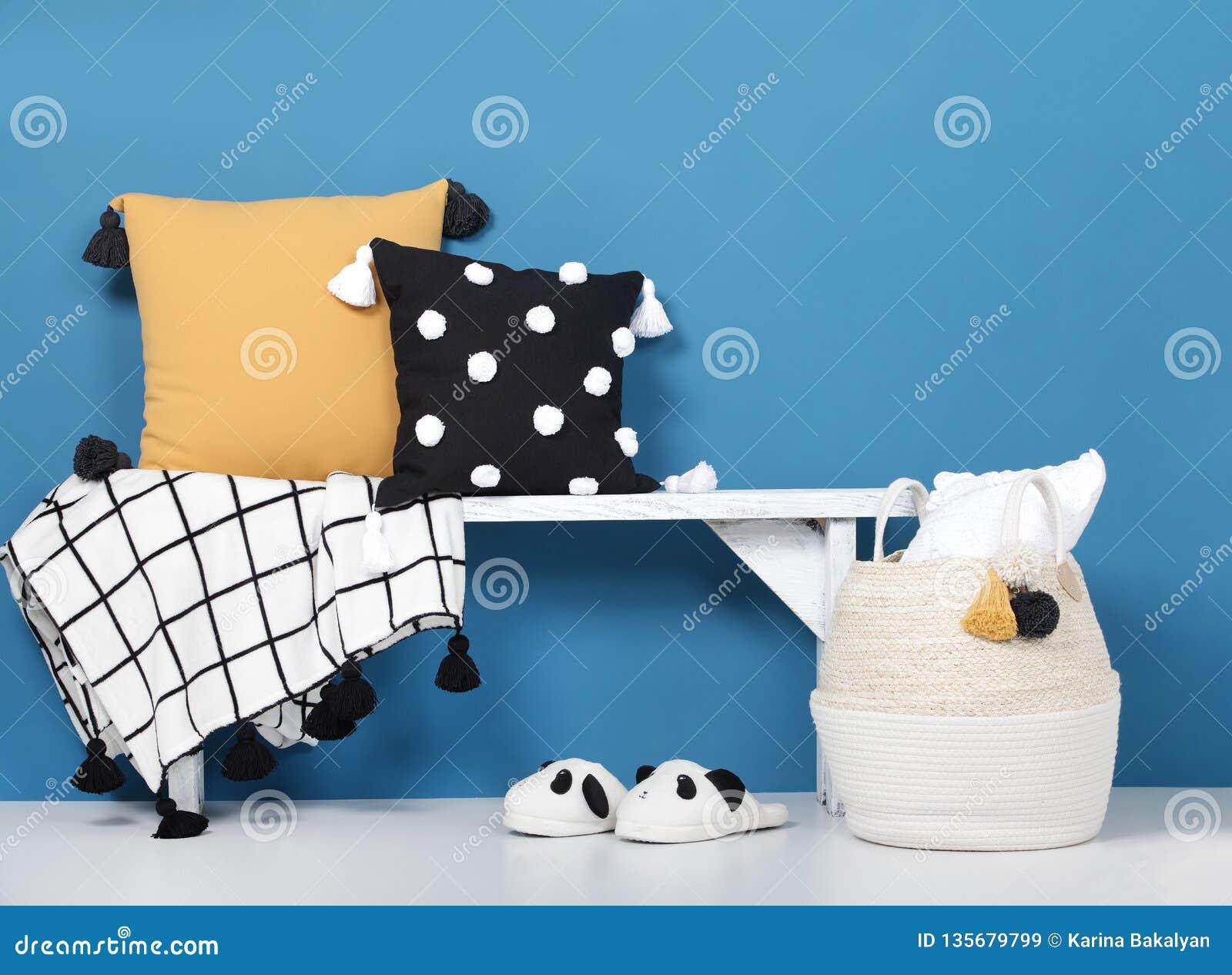 Dekorativ kuddar och filt med pom-poms på en träbänk, hemtrevliga mjuka häftklammermatare och en vide- korg