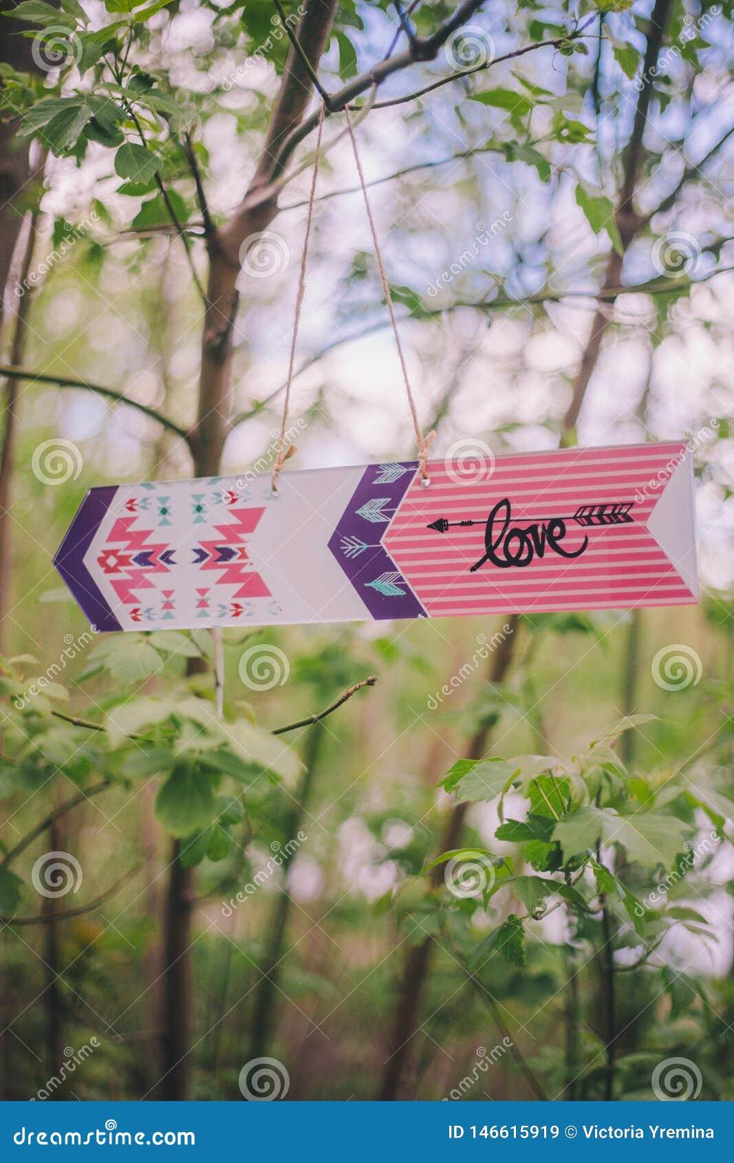 """Dekorativ pil-pekare för närbild med inskriften """"love"""" som hänger på filialträd på naturen"""