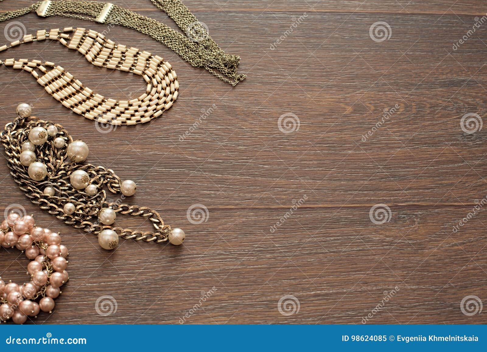 Dekorativ sammansättning av smycken för kvinna` s på trämörk bakgrund