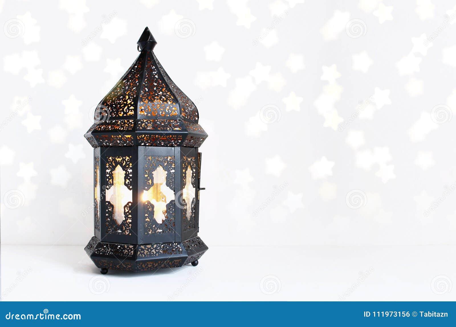 Dekorative dunkle marokkanische, arabische Laterne auf der weißen Tabelle Brennende Kerze, funkelndes bokeh beleuchtet Sterne gru