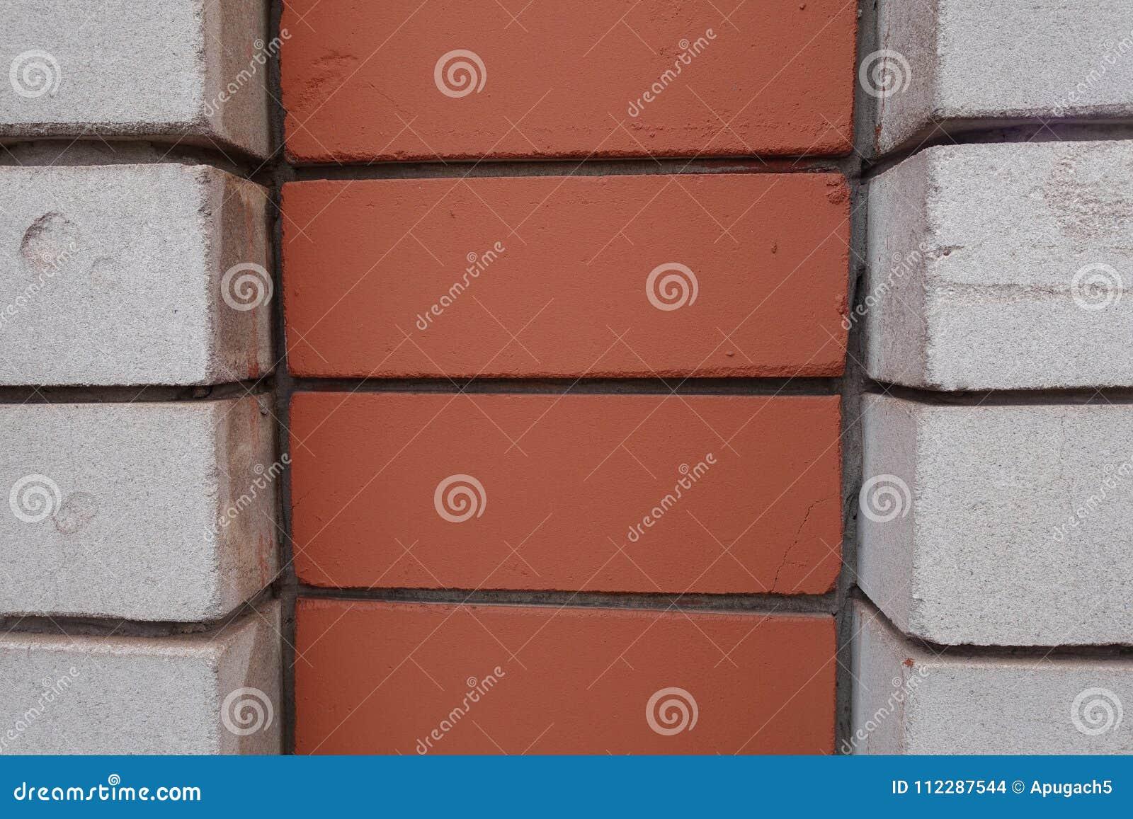 Dekorative Maurerarbeit gemacht von den weißen und orange Ziegelsteinen