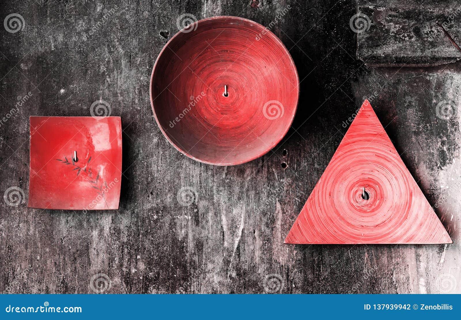 Dekorative Platten von verschiedenen Formen auf strukturierter Wand des alten Schmutzes Lebende korallenrote Farbe der Zusammenfa