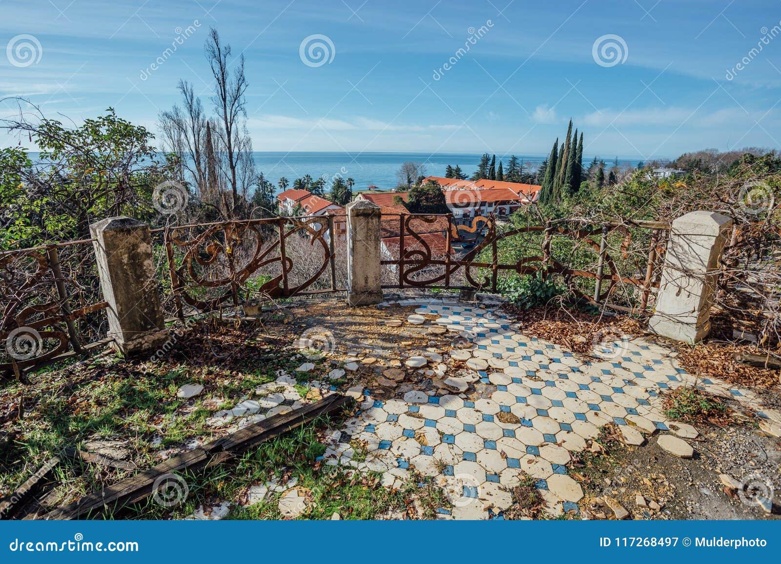 Dekorativer gebrochener Fliesenboden und Balkon mit rostigem dekorativem Gitter an verlassener Villa Ansicht zum Meer von verlass
