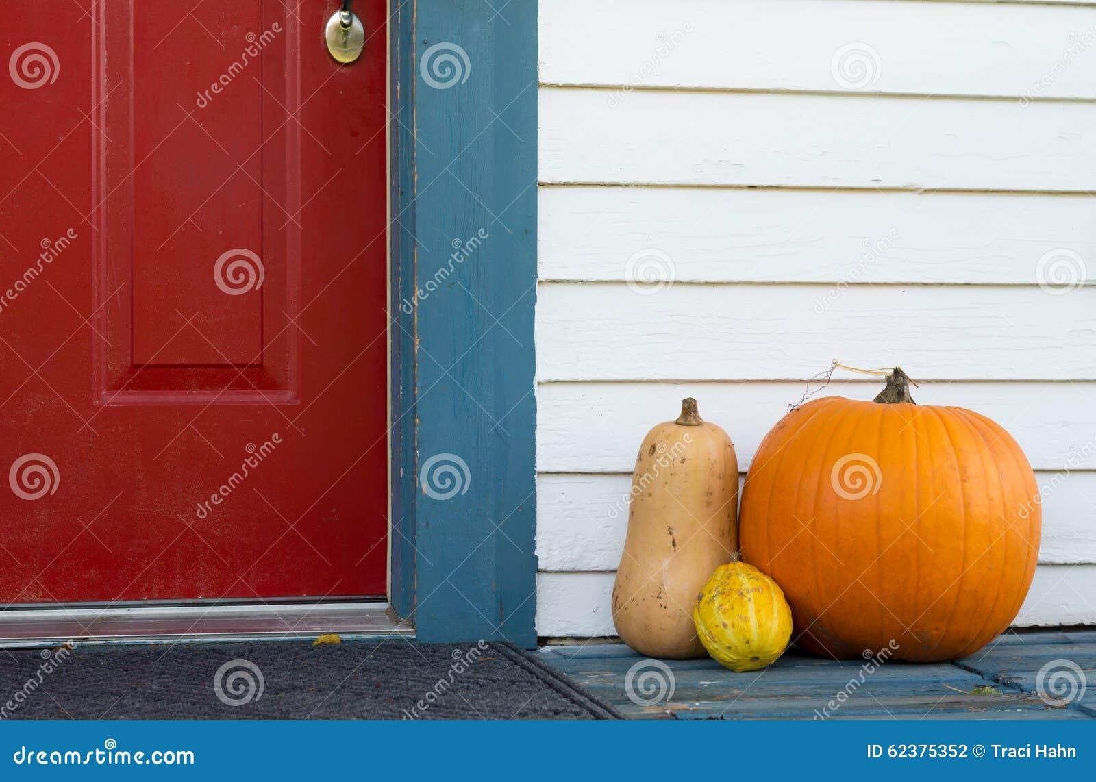 Dekorativer Kürbis und Kürbisse auf der Eingangsterrasse eines Hauses