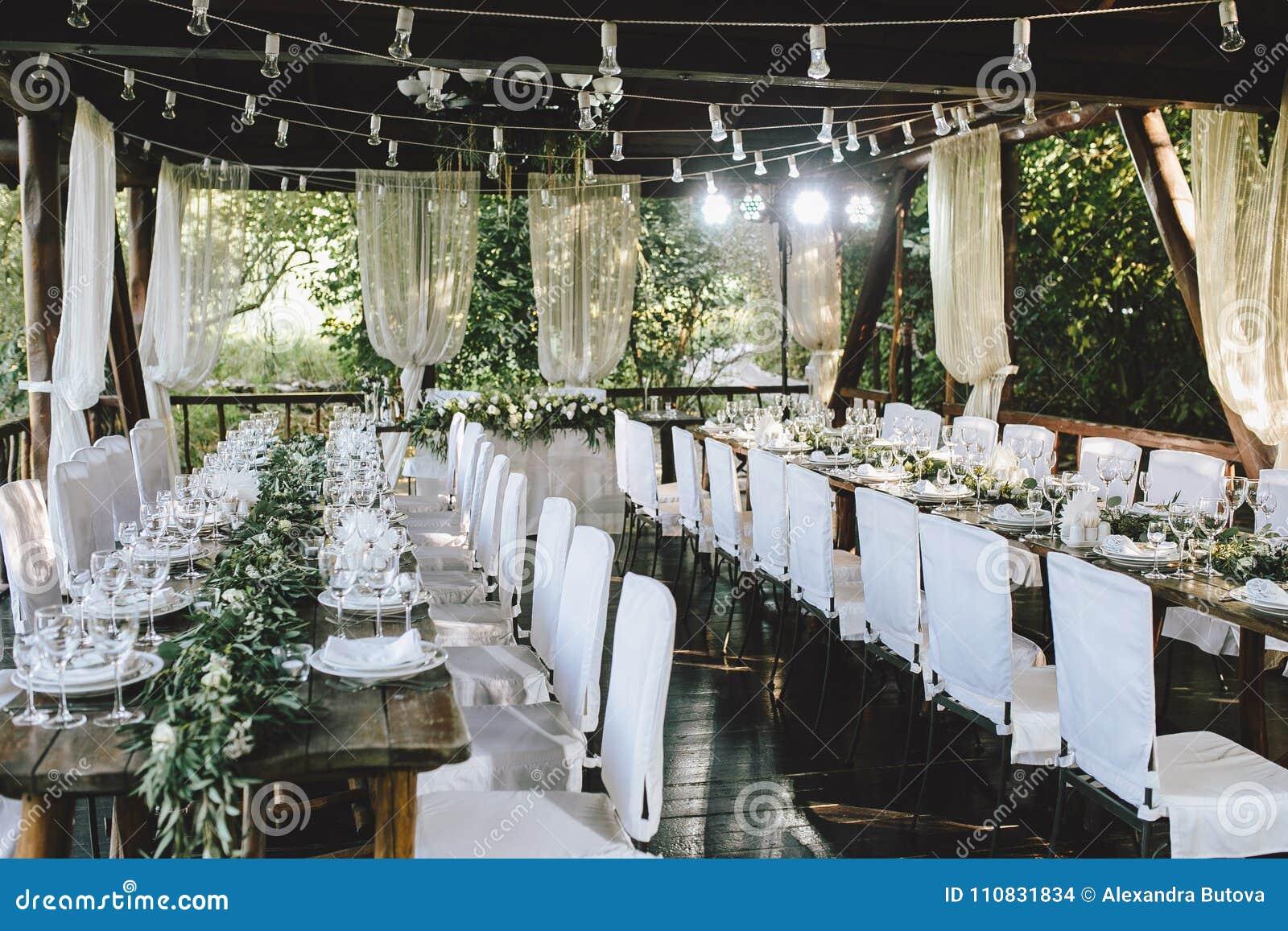 Dekorerad elegant träbrölloptabell för banketten som är utomhus- i trädgårds- gazebo med lampan, i stilen av lantligt med eukalyp