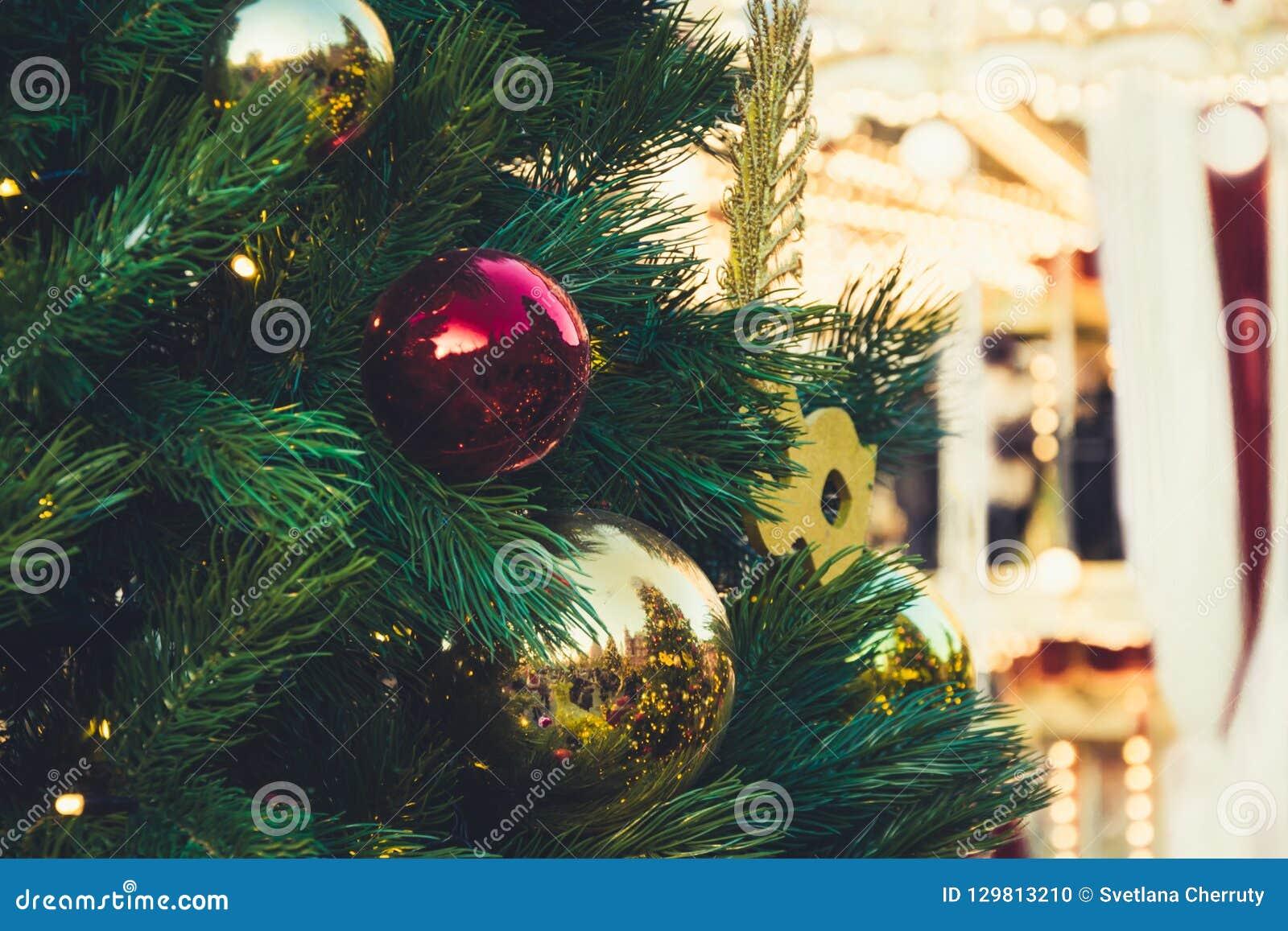 Dekorerad julgran med röda bollar och girlanden Utomhus- mässa Xmas-karusell close upp Vinter