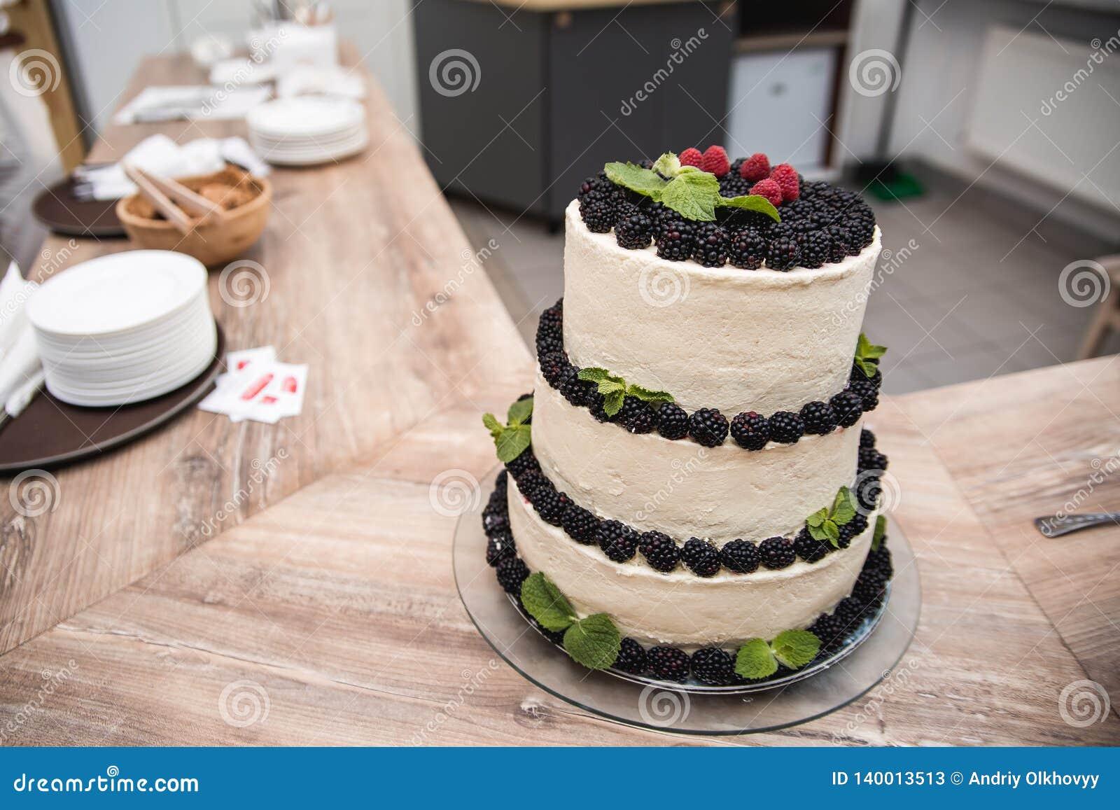 Dekorerad naken bröllopstårta med röda bär och en damning av florsocker