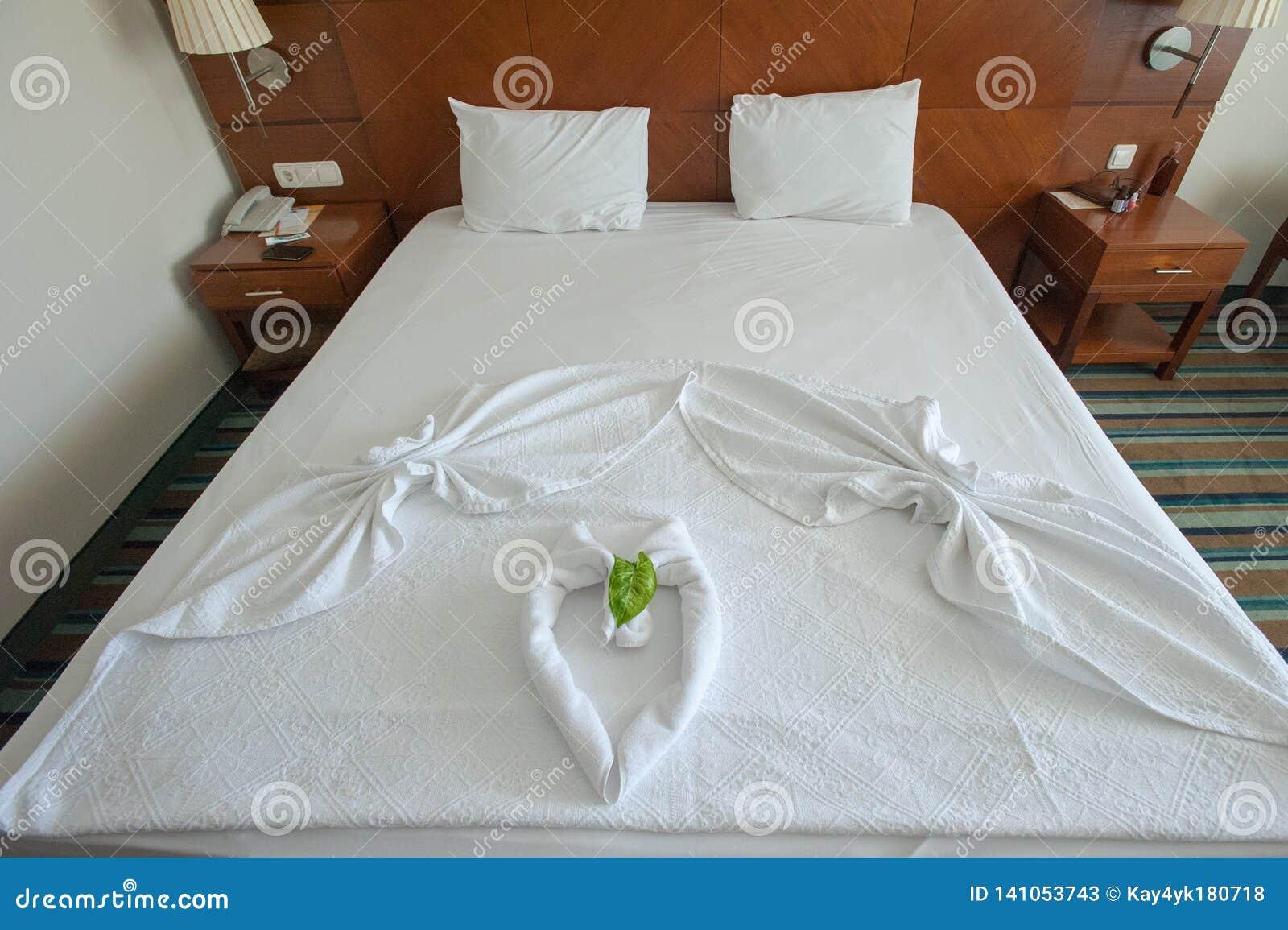 Dekorerad säng med handdukar och hjärta-formade räkningar