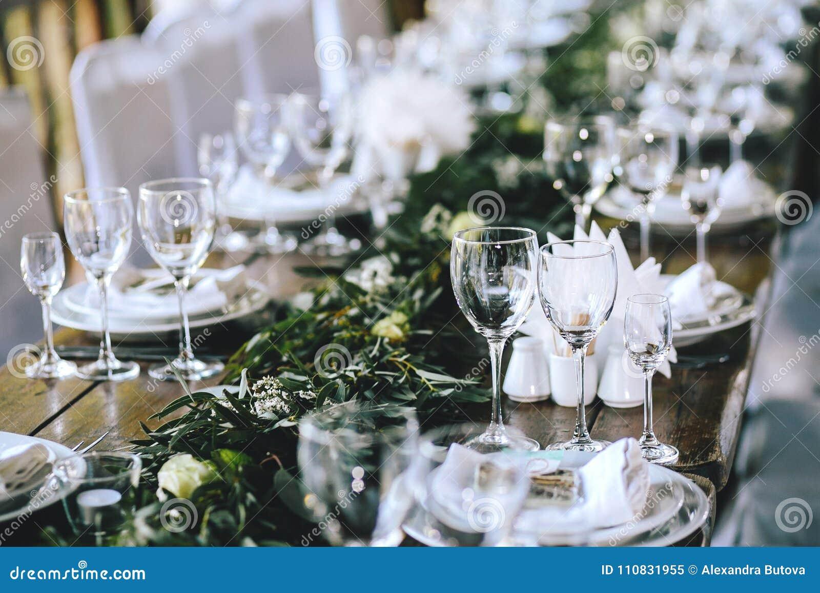 Dekorujący elegancki drewniany ślubu stół w wieśniaka stylu z eukaliptusem, kwiaty, porcelana talerze i szkła,