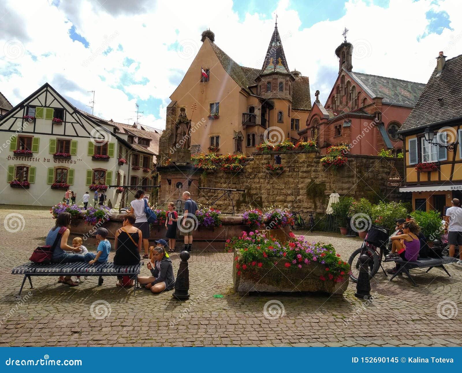Dekoruję z kwiat fontanną w głównym placu Eguisheim otaczał typowymi domami Alsace, Francja