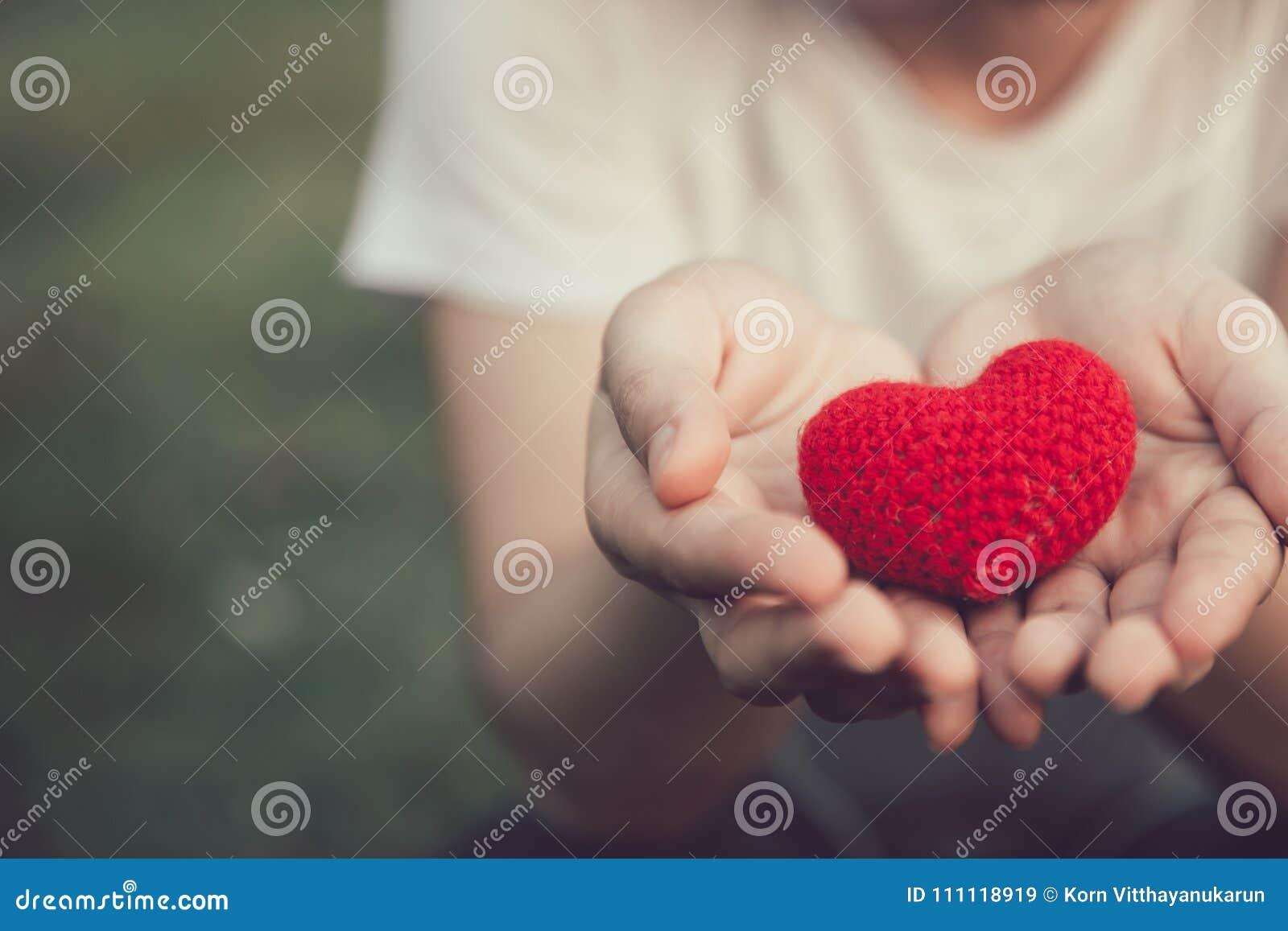 Dela röd färg för förälskelse och för hjärta på kvinnahanden