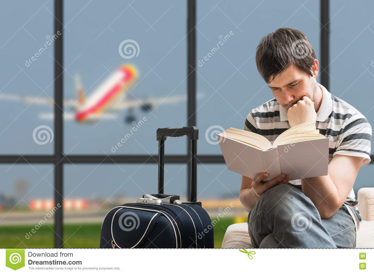Delayed aeroplane concept. Man is sitting with baggage in airport