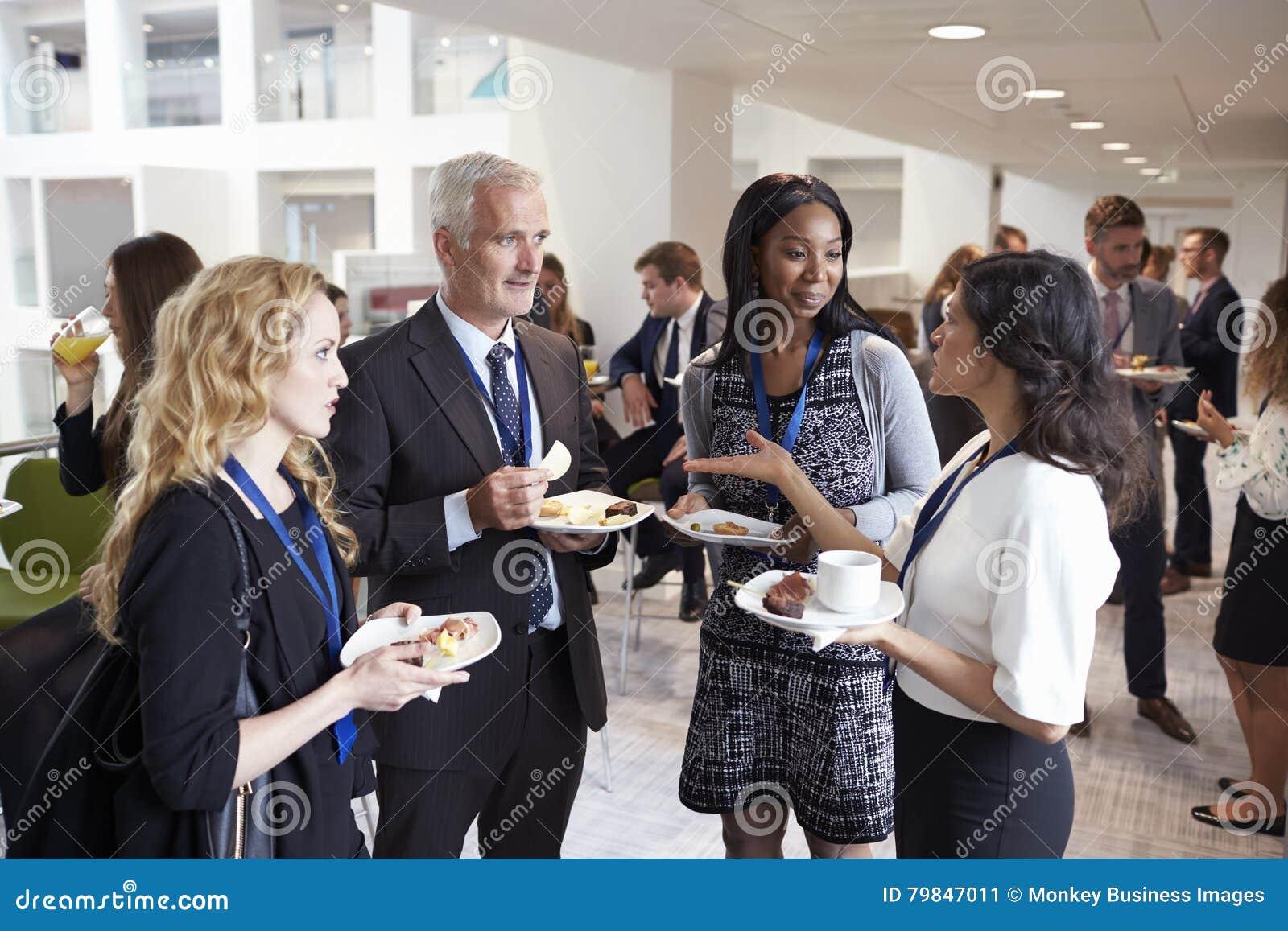 Delegater som knyter kontakt under konferenslunchavbrott