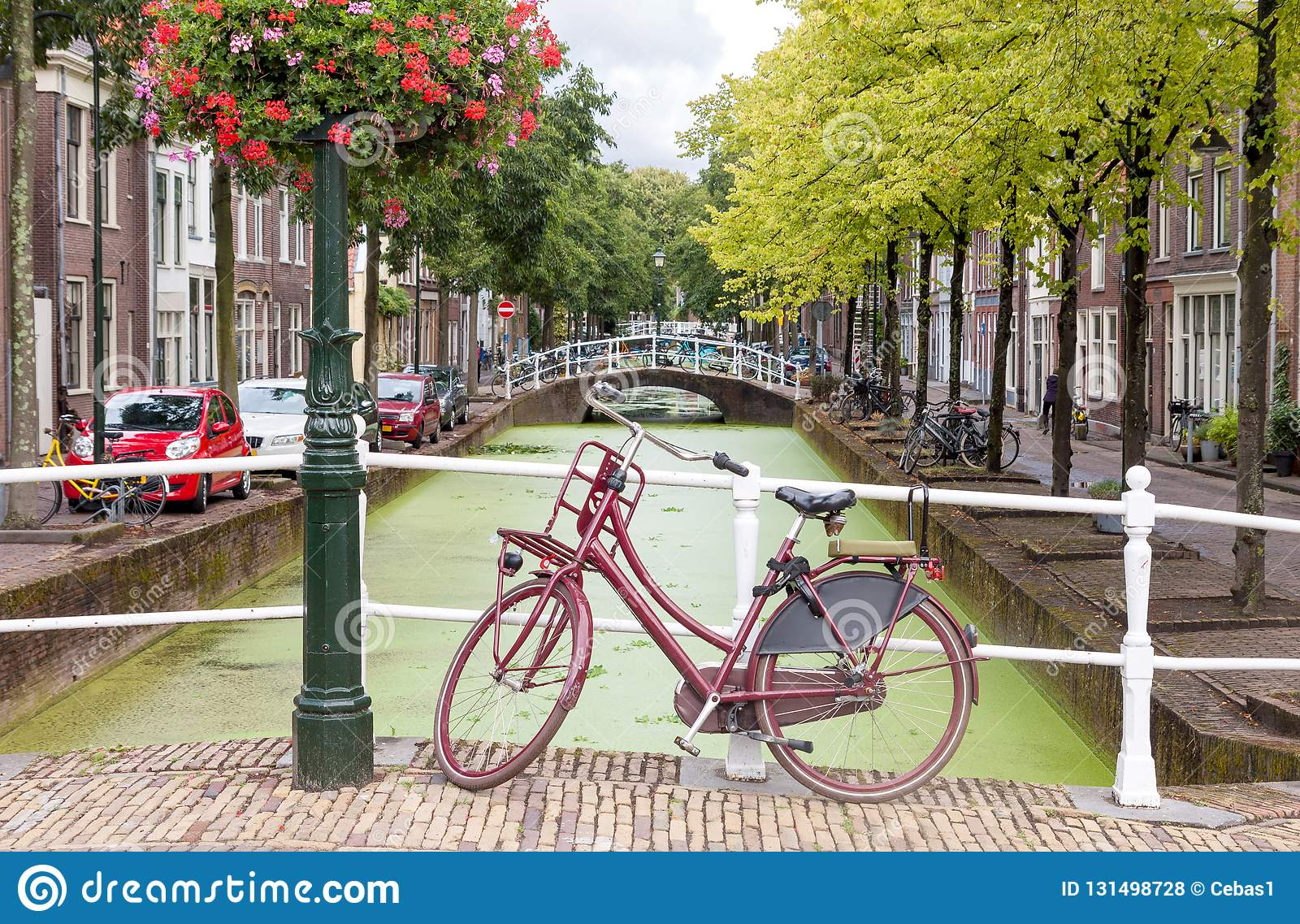 Delft city view in the Netherlands with water canal and vintage bicycle