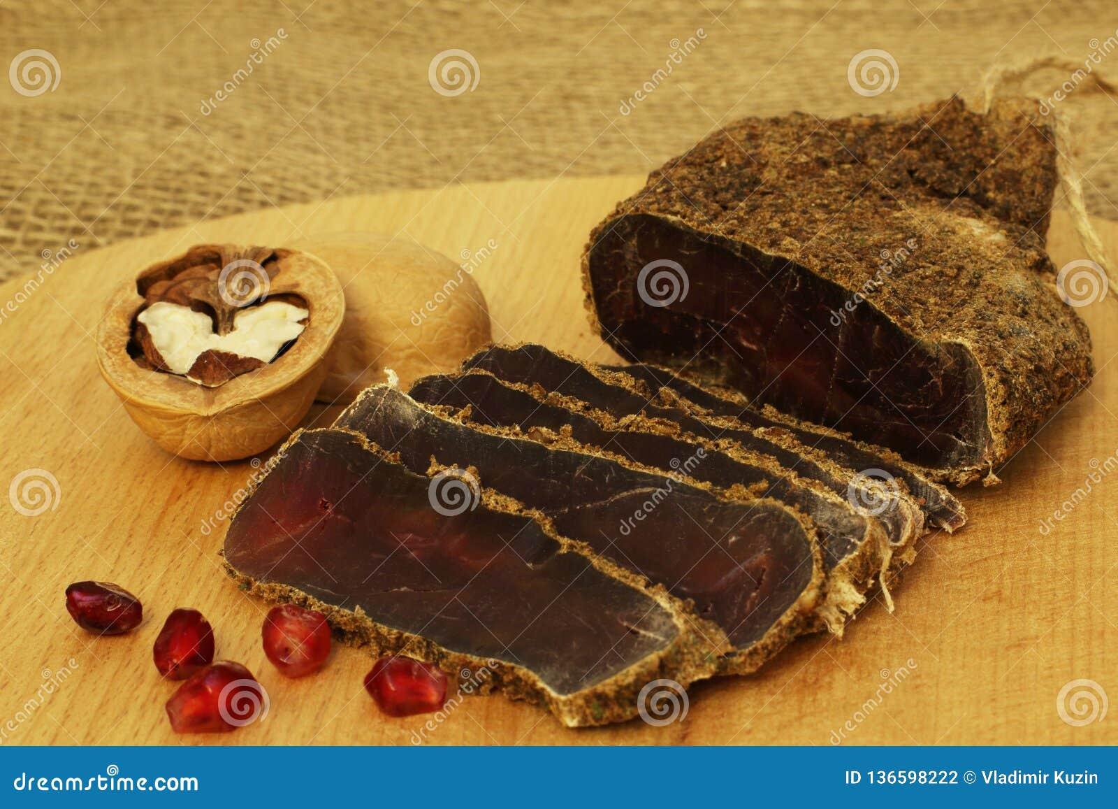Delicacy Carne salgada secada picante apetitosa perfumada deliciosa com as especiarias com as sementes e as nozes vermelhas da ro