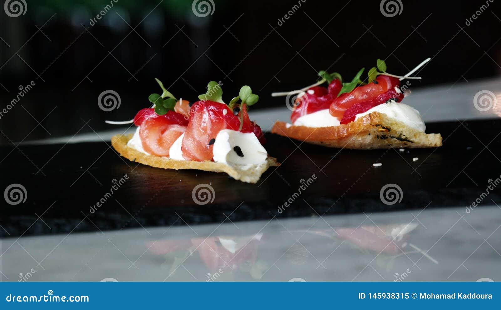Delicioso divirta o aperitivo do bouche, salm?es curados com beterrabas, xadrez e a flor alaranjada