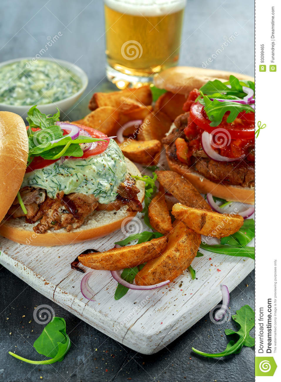 Delicious Bagel Pork sandwiches with vegetable and Tzatziki Sauce and Fries on white board.