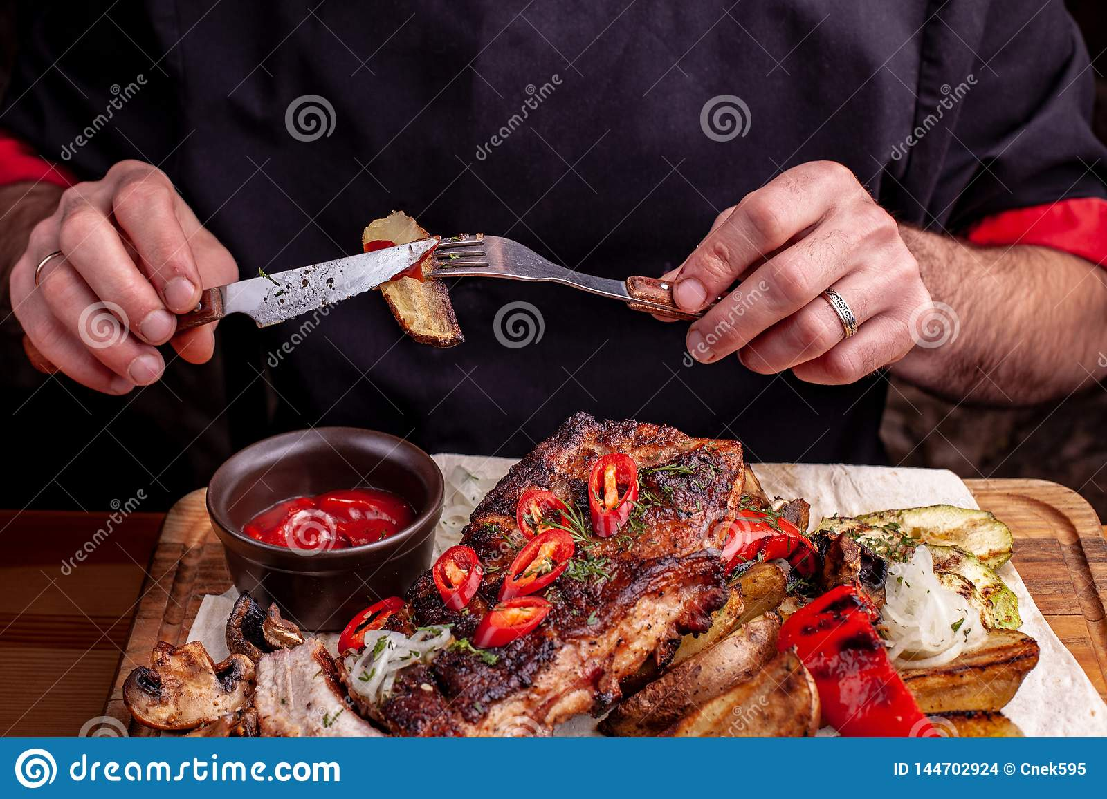 Delicious barbecued ribs seasoned with fresh herbs, cabbage salad, backed potato on an old rustic wooden chopping board