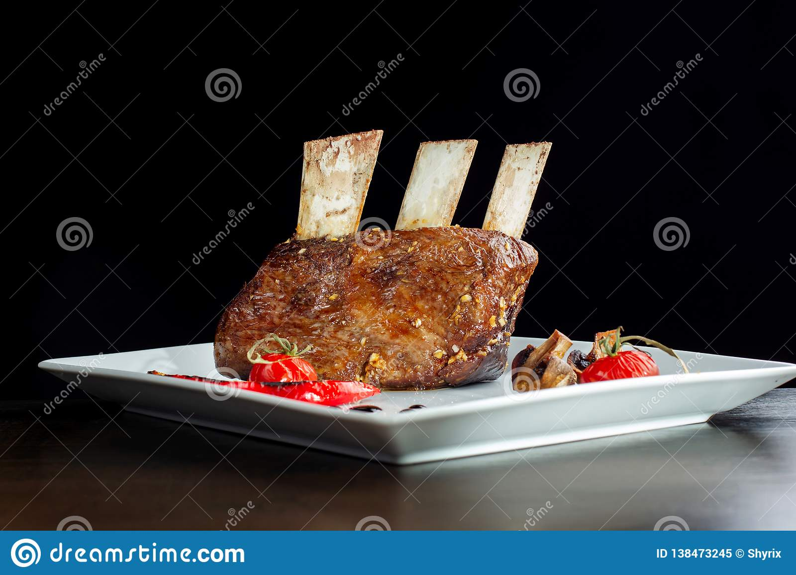 Delicious barbecued ribs seasoned served with mushrooms on a white plate.