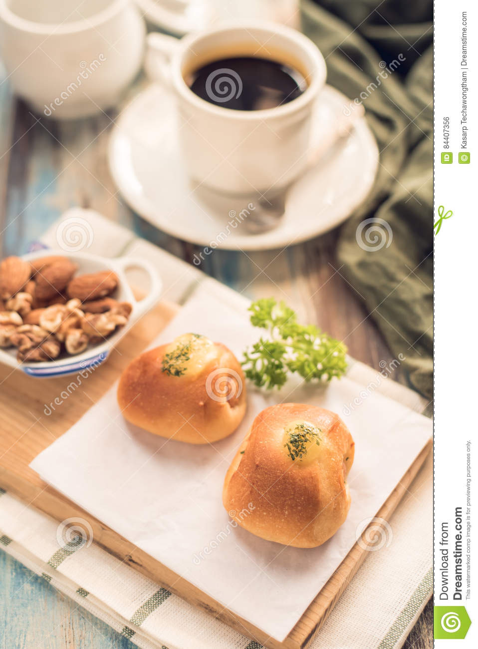 Delicious breakfast. Served with bread, Sausage Rolls black coffee and nut, on Wooden table. Top view. View from above. Selective