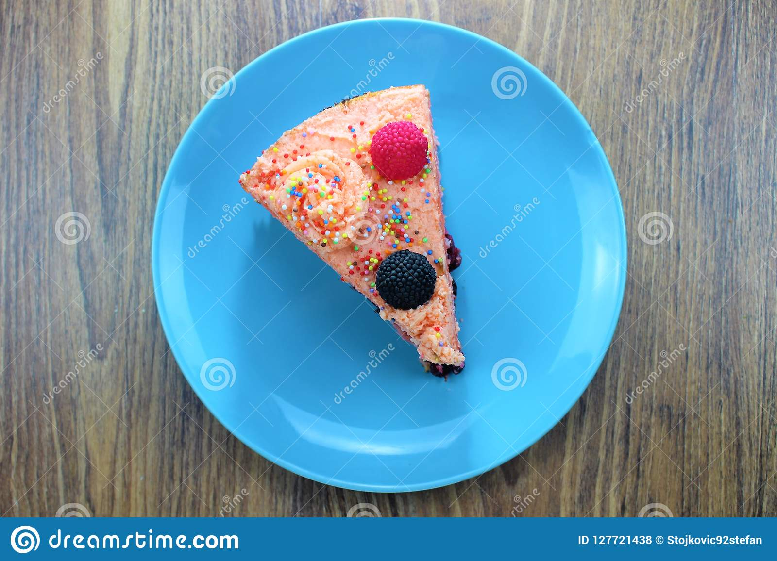 Delicious cake on a blue and white plate with chocolateTasty cake with strawberries, blackberries and colorful sprinkles on the bl