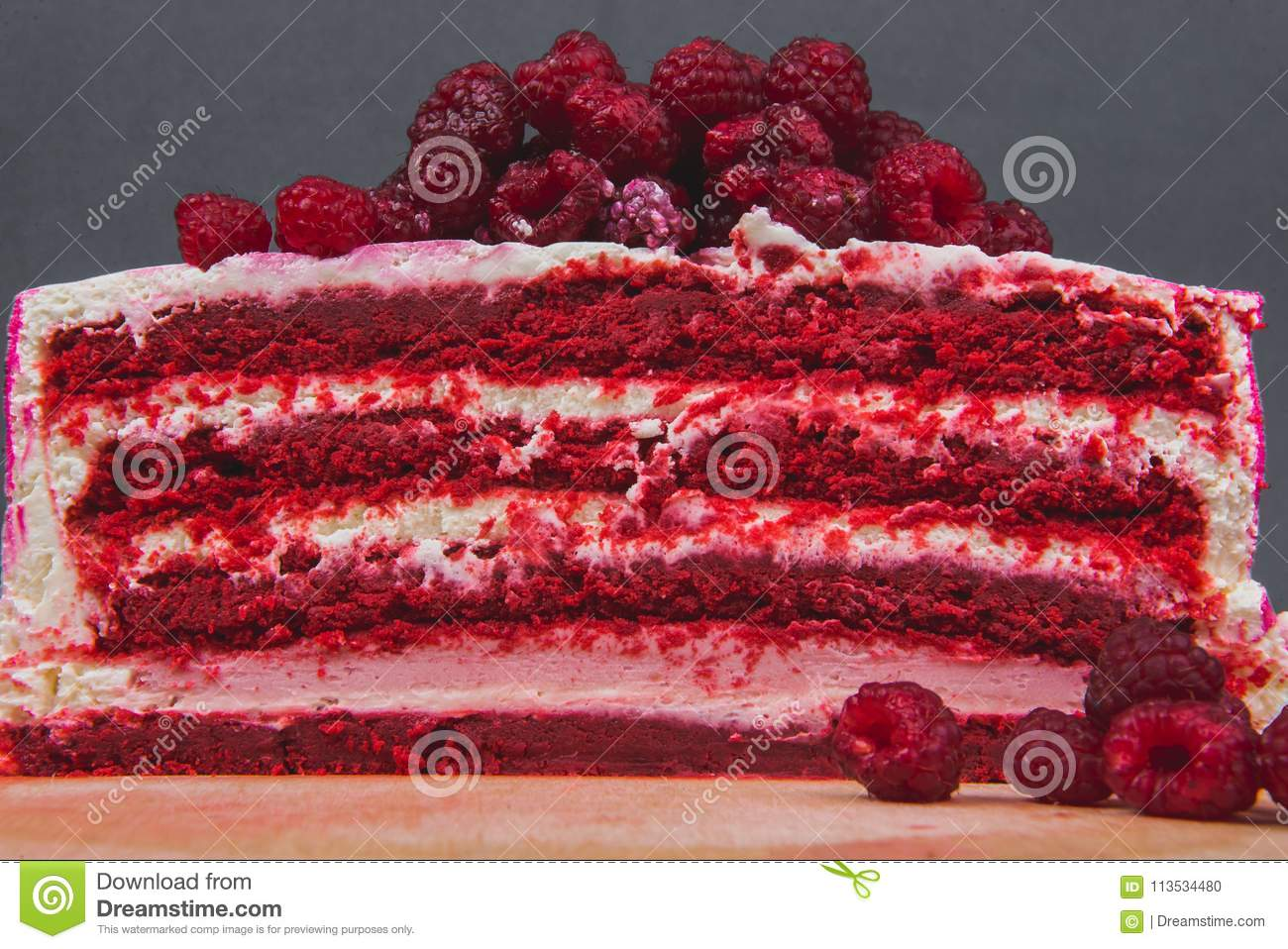 A delicious cake decorated with raspberries on a gray background.
