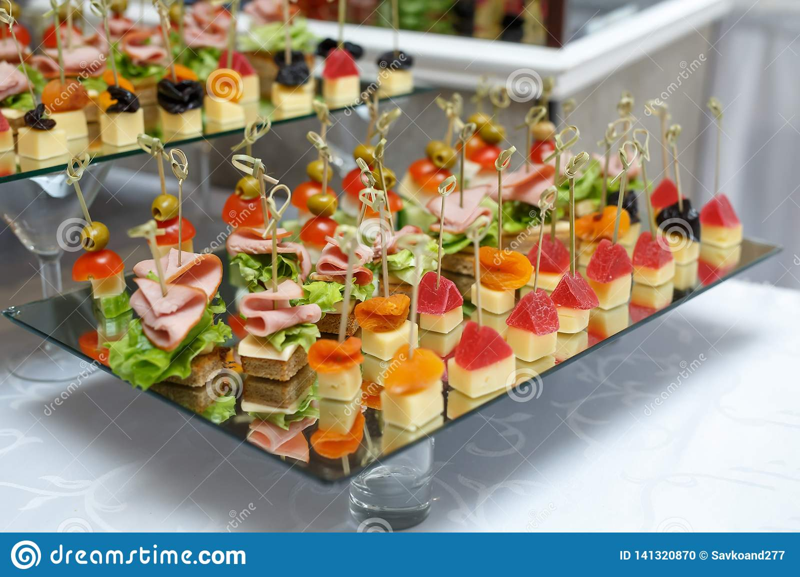 Delicious canapes with ham, cheese and fruit