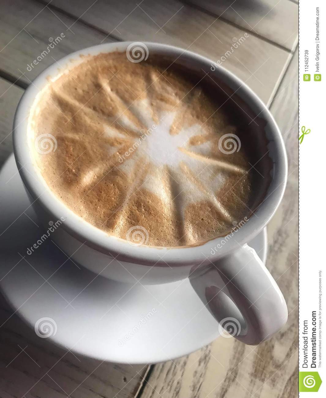 A delicious cappuccino in a Porzellan cup. Placed on a wooden table