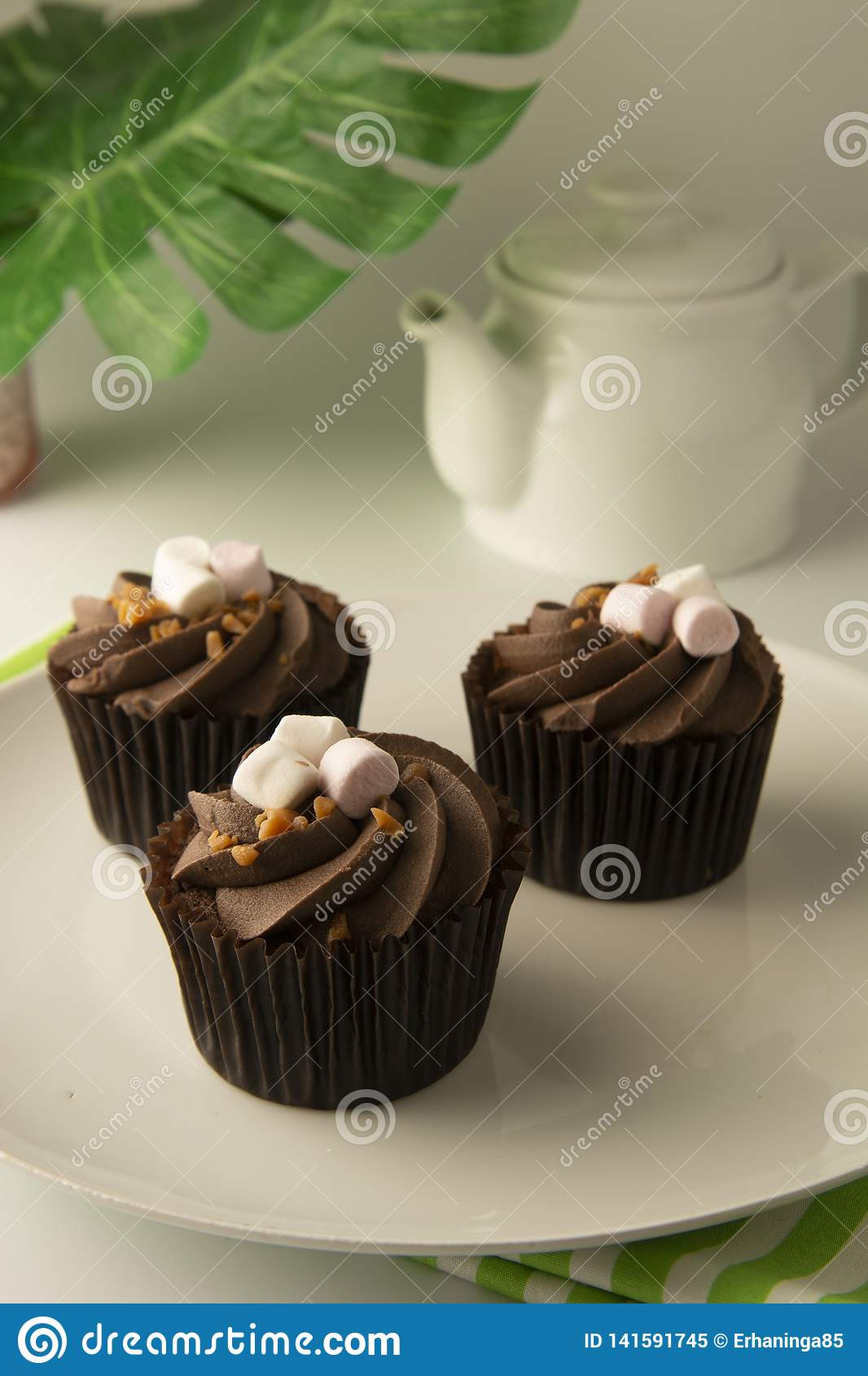 Delicious chocolate cupcake dessert. Brownie cake with cream. Sweet dessert. Monstera green leaves on background