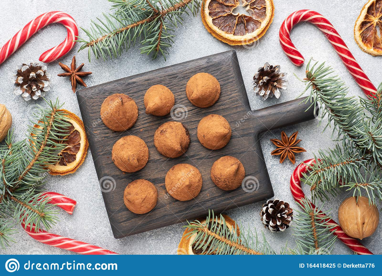 Delicious chocolate truffles sprinkled with cocoa powder on a wooden stand. Christmas tree scenery concept