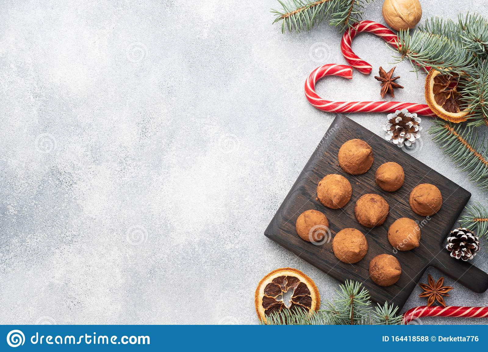 Delicious chocolate truffles sprinkled with cocoa powder on a wooden stand. Christmas tree scenery concept. Copy space