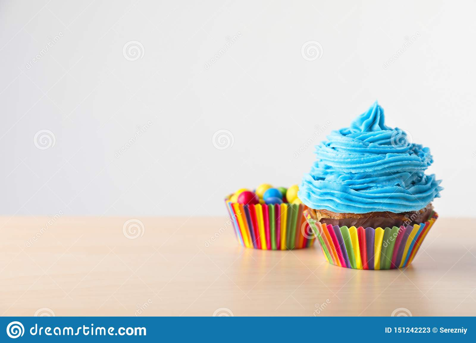 Delicious cupcake with candies on light wooden table
