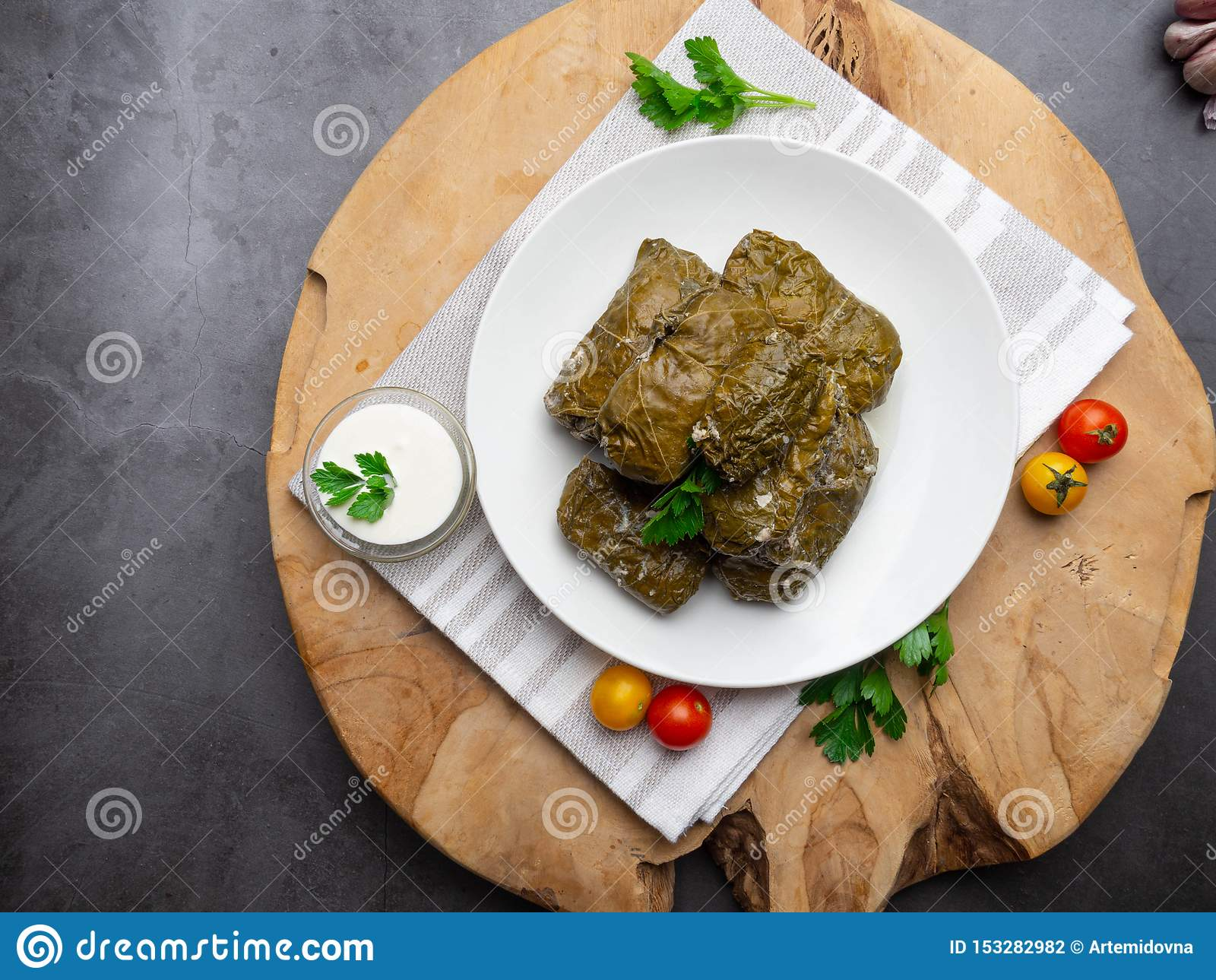 Delicious dolma sarma stuffed grape leaves rice, white yogurt sauce. Lebanese dolma sarma on plate. Lebanon turkish greek middle