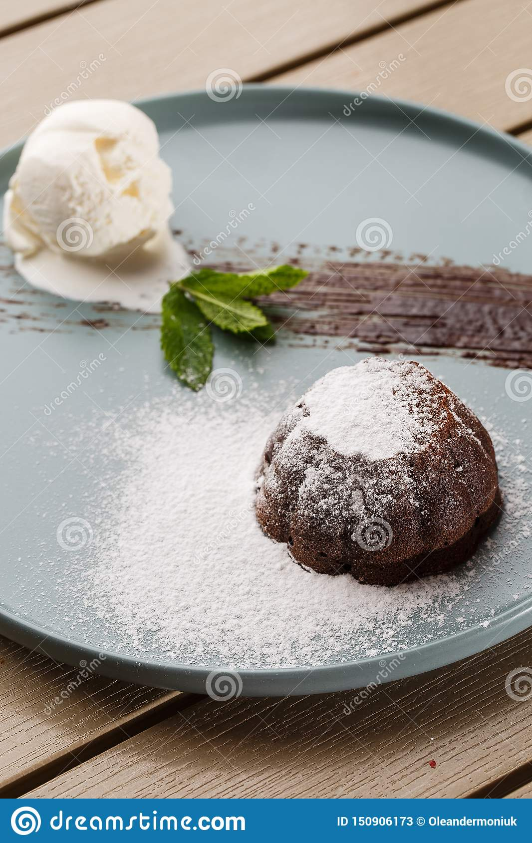 Delicious fresh fondant with hot chocolate and ice cream and mint served on plate. Lava cake recipe. Wooden background.