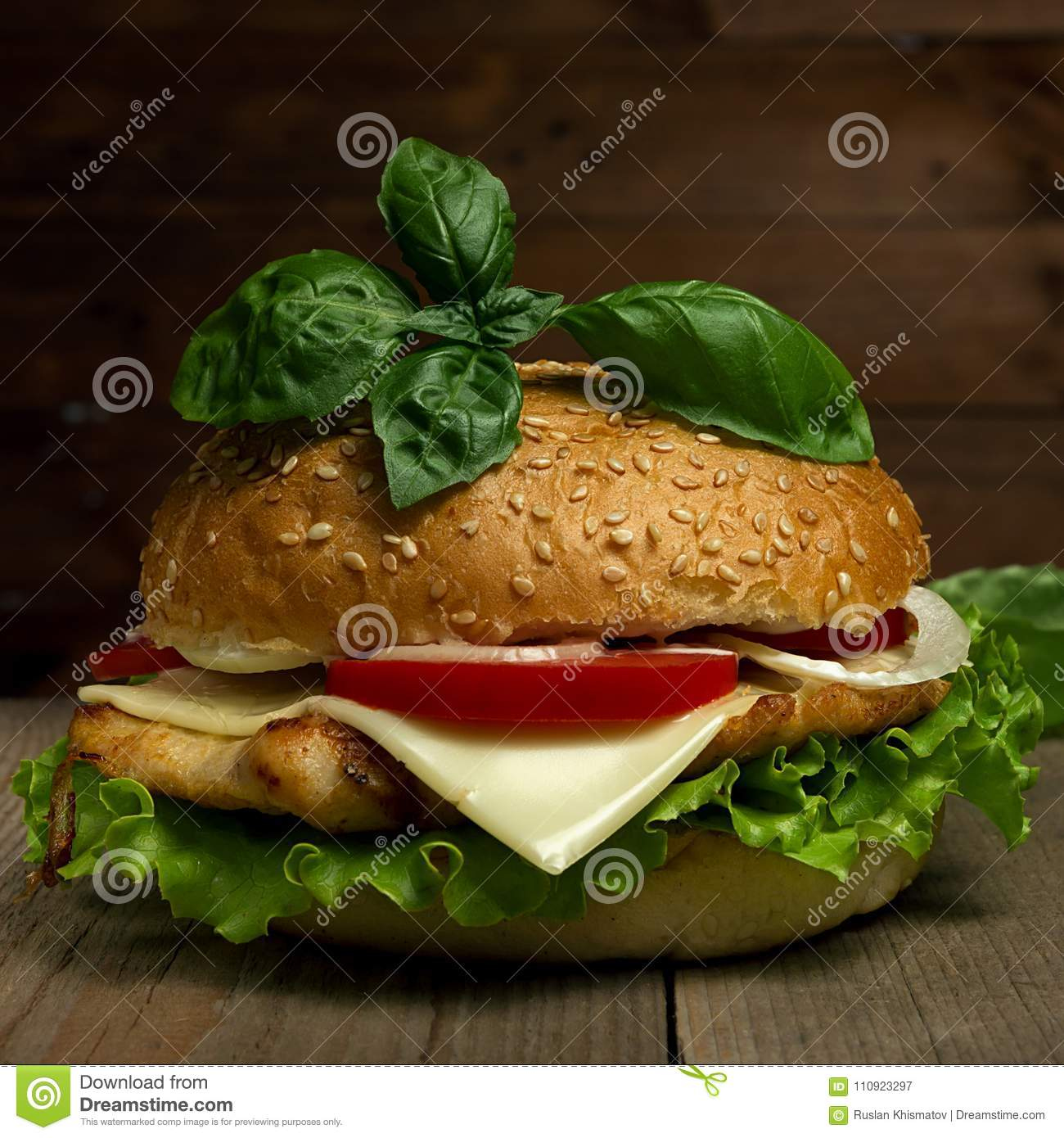 Delicious hamburger with cheese, tomatoes and basil on wooden background. Fastfood meal.