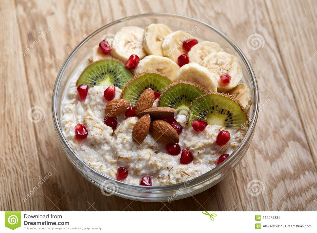 Delicious oatmeal porrige with fruits in glass bowl over rustic wooden background, shallow depth of field, close-up.