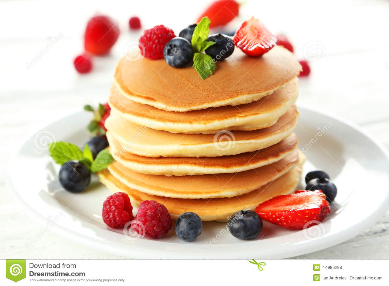 Delicious Pancakes With Berries On A White Wooden
