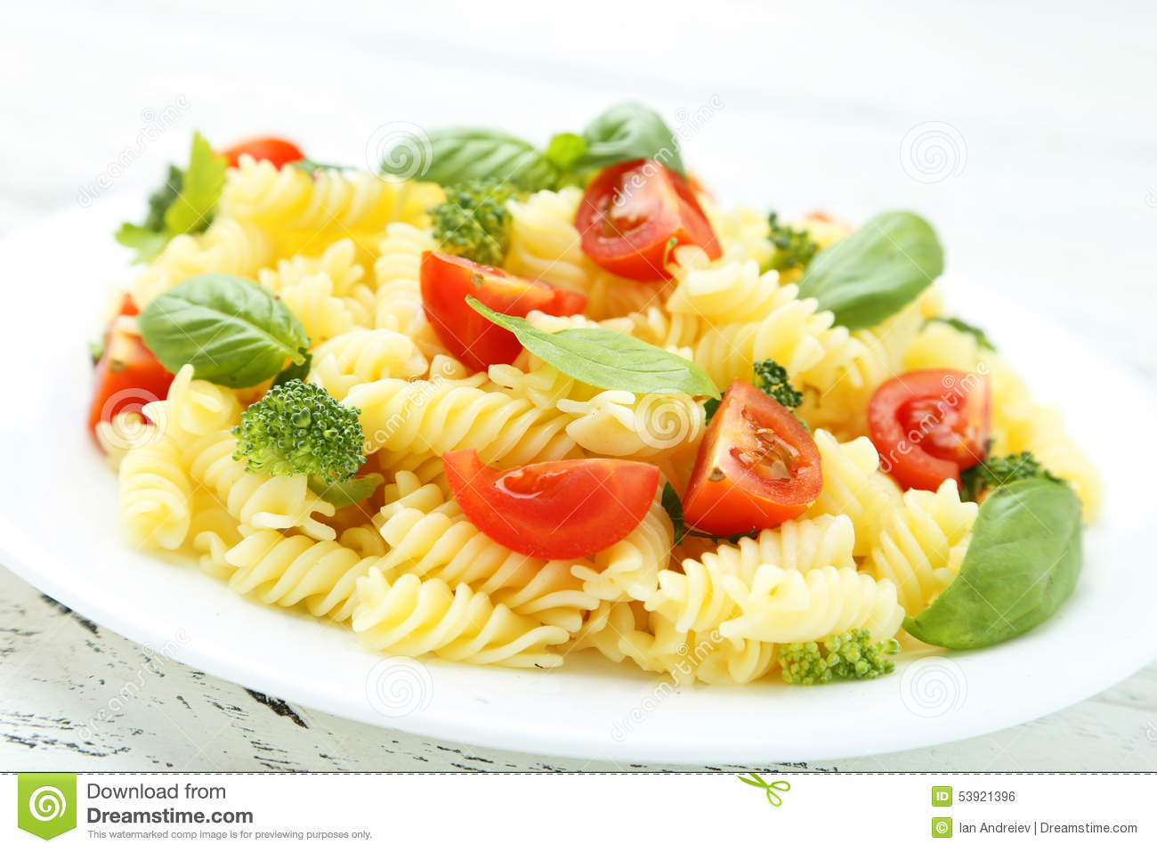 Delicious pasta on plate on white wooden background.
