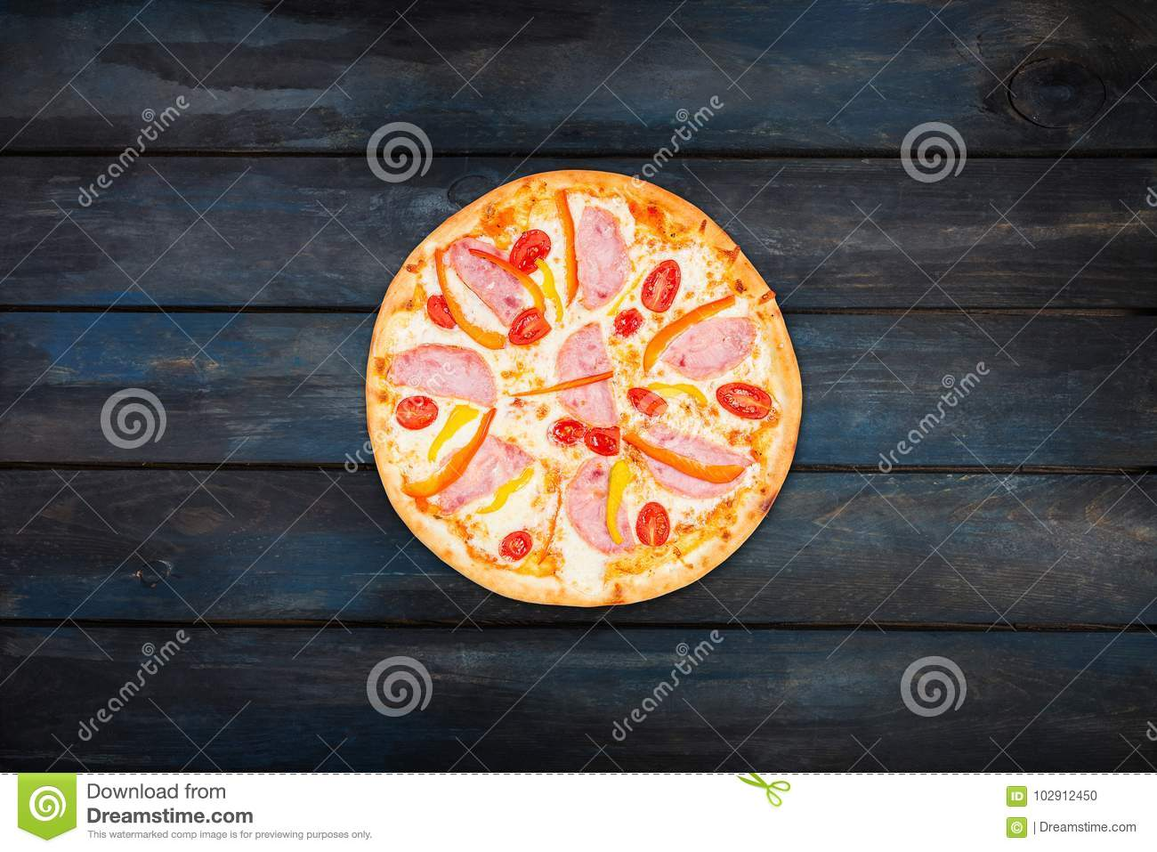 Delicious pizza with ham sweet peppers and tomatoes on a dark wooden background. Top view center orientation