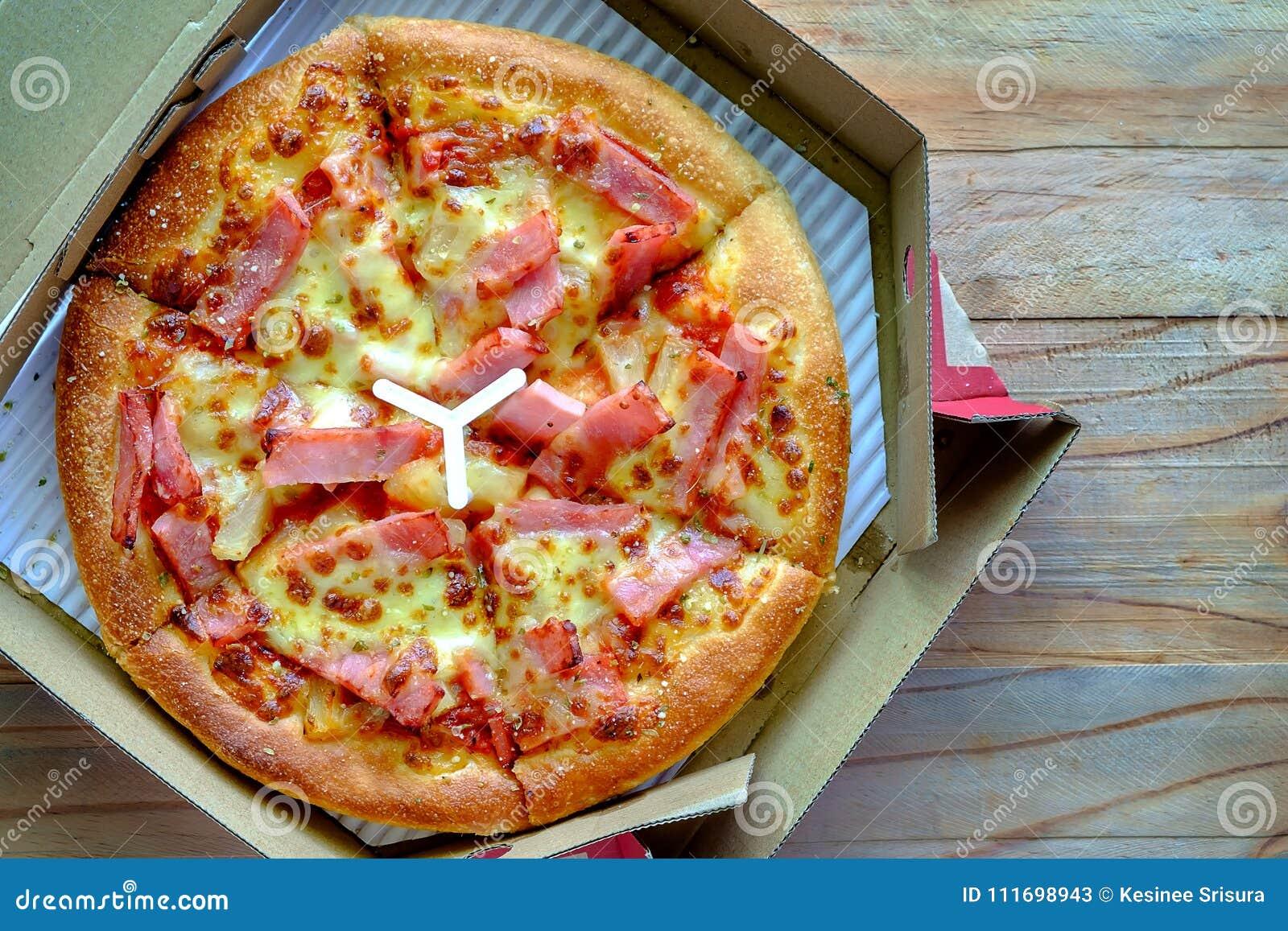 Delicious pizza with pineapple, ham slice, bacon slice, mozzarella cheese, pizza sauce in a delivery box