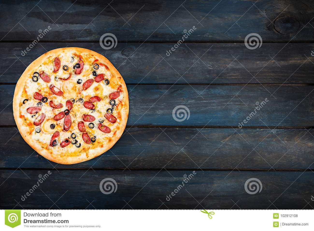 Delicious pizza with smoked sausage and olives on a dark wooden background. Top view orientation on the left side