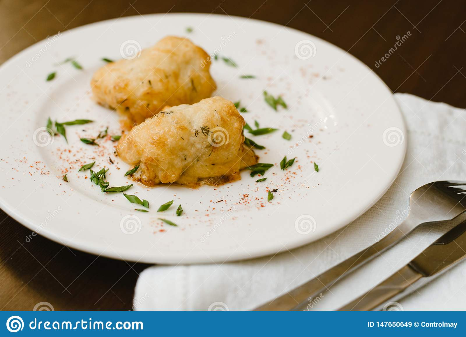 Delicious rolls of dough with grass on a plate.